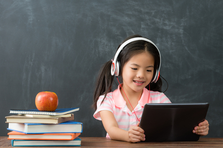 Photo pour happy beautiful little girl student sitting in blackboard background and using mobile pad computer studying through online e-learning system. - image libre de droit