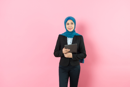 Photo pour professional happy muslim business woman holding mobile pad computer face to camera isolated on pink background. - image libre de droit