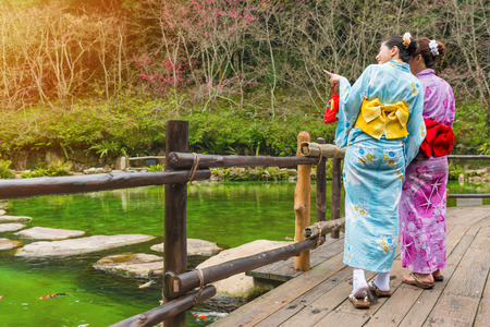 back view photo of young beautiful women friends pointing landscape when they wearing kimono walking on wooden walkway viewing pool in sakura garden park.