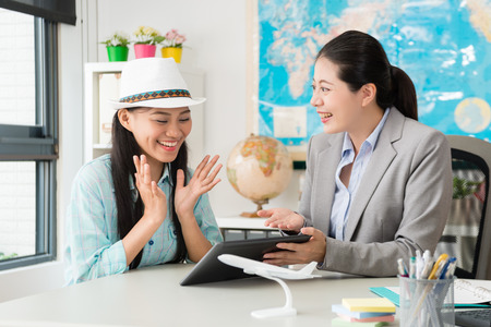 Photo pour cheerful elegant female customer feeling happy when travel agent company manager woman using mobile pad computer showing special price for her. - image libre de droit