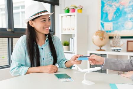 Foto de smiling pretty woman traveler giving credit card for travel agent when she booking itinerary. - Imagen libre de derechos
