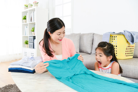 Photo pour elegant beauty housewife folding family clothing in living room and her little daughter feeling surprised. - image libre de droit