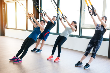 team of Asian people training with total body resistance exercises together in the sunshine classroom of the gym.