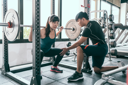 Foto de Woman doing squats with barbell. The personal trainer helping her flexing muscles in Smith machine in gym. - Imagen libre de derechos