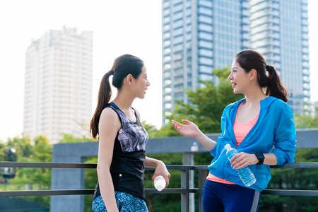 Foto de Two healthy female runners taking a break chatting with city background after running in the morning. - Imagen libre de derechos