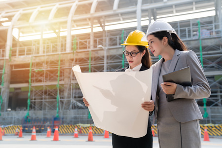 Photo for Two female engineers checking construction plan on site. Seriously staring at the blueprint of the building. - Royalty Free Image