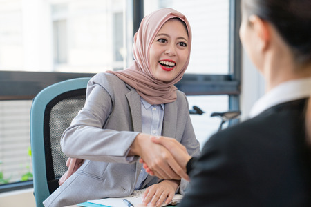 Photo pour A Muslim young businesswoman is happy about the deal. They shake their hands to celebrate their good partnership. - image libre de droit