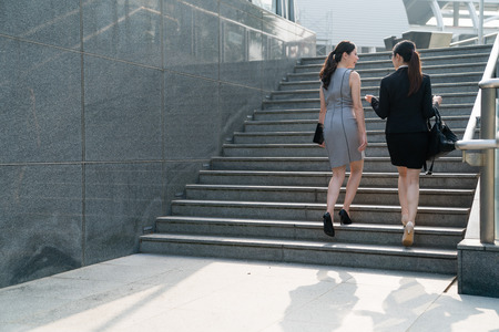 Foto de Two Asian office lady walk up the stairs and discuss with each other. On a back view. They both wearing high heels and formal suits dress carrying bags. Talking about the business stuff and costumers. - Imagen libre de derechos