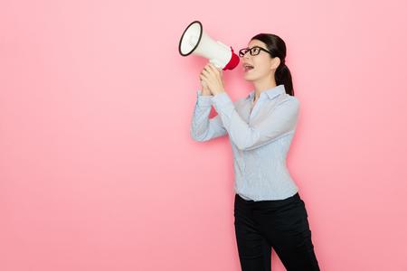 Foto de business lady using loudspeaker talking isolated on pink background - Imagen libre de derechos