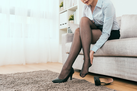 Foto de businesswoman back home and feel foot heel painful after the walk with high heel shoes - Imagen libre de derechos