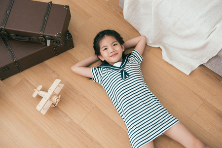 Photo for kid lying on her back and looking up in the room. She seems very relaxing. - Royalty Free Image