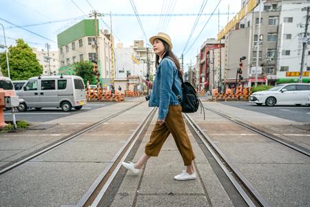 Foto de relaxed travel woman walking across the railroad holding her phone in osaka city in japan. - Imagen libre de derechos