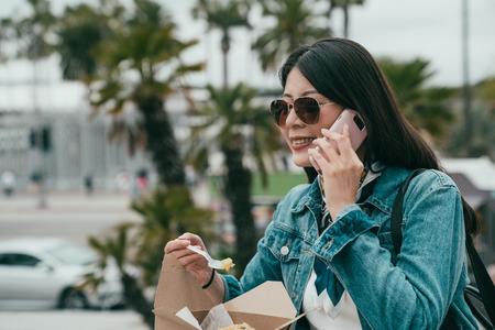 elegant lady chatting with her friend on the cellphone while having lunch. they must talk about something funny because the woman is smiling attractively