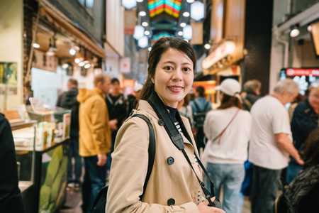 pretty female photographer face to camera smiling attractively while taking pictures in the traditional market. attractive woman standing in crowd. spring holiday travel in Japan.