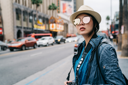 Photo pour elegant female traveler standing on the street and waiting for taxi to go back to hotel. woman in straw hat and sunglasses looking at the road. cool weather in LA. - image libre de droit
