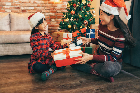 Photo for Young mother and her daughters on the wood floor by christmas tree at home. attractive santa girls exchanging gift in living room on Xmas Eve. celebrate christmas at home concept. - Royalty Free Image