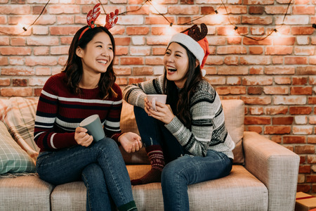 Foto de young girls chatting and having fun at home. relaxing celebrating xmas holiday concept. best friends with santa hat and deer cheerful laughing. - Imagen libre de derechos