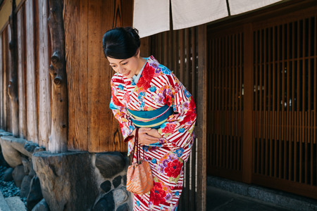 Foto de Japanese lady bowing in front of her house with beautiful kimono. traditional lifestyle in jp. attractive woman with colorful kimono clothing in summer. - Imagen libre de derechos