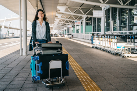 Foto de businesswoman walking fast through the luggage cart and rolling car. young lady going to work abroad visiting clients. elegant woman outside international airport with trolley in sunny day. - Imagen libre de derechos