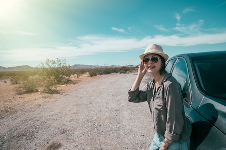 female car driver standing on the empty nature sunny day relying on the black car. young woman with straw hat and sunglasses enjoy the beauty of the wild during the trip. asian lady self driving tour