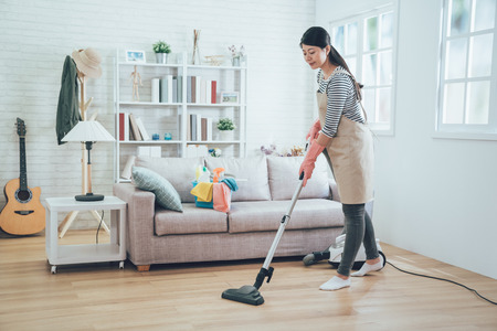 Photo for asian lady doing house chores in apron. young housewife using vacuum cleaner cleaning the wooden floor in the living room. happy housekeeper doing housework at home with attractive smile on face. - Royalty Free Image