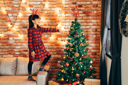Foto de adorable girl kid in reindeer decorating christmas tree with baubles at home. little child standing high on sofa holding golden ball. lights hanging on red brick wall in background. - Imagen libre de derechos