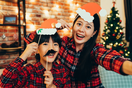 Photo pour sweet family having fun playing with paper decoration making funny face taking selfie at home celebrating christmas eve. cute santa girls enjoy cheerfully spending time together on holiday. - image libre de droit