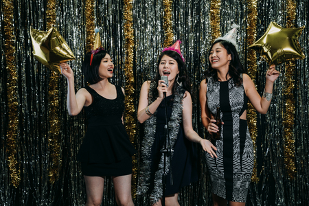 attractive ladies cheerfully enjoying music at nightclub in karaoke party. young girls dancing having fun playing with gold star balloons. beautiful women wearing funny hats performing on stage.の写真素材