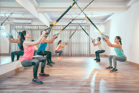 Foto de group of young asian people doing squat with fitness suspension straps. healthy sporty friends working out in a sunny bright gym. five students in training lesson concentrated doing exercise. - Imagen libre de derechos