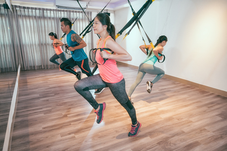 Foto de young asian people doing elastic rope exercises crossfit room pulling with all of body power. group of happy friends working out together in gym taking total body resistance exercise lesson. - Imagen libre de derechos