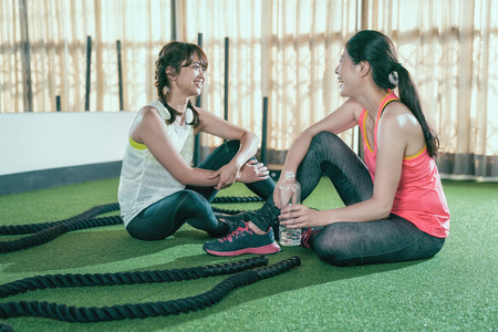 Photo pour female athletes sitting chatting resting while taking a break after battle rope training lesson. tired sweat women drinking bottle water health love sports. two friends cheerfully laughing in gym. - image libre de droit