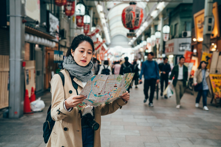 Photo pour asian female tourist holding tourism city map in osaka city japan walking in the teeming market in the morning. huge red lanterns hanging on the roof indoors in shopping area. - image libre de droit