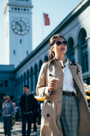 Photo pour young lady traveler holding coffee cup walking sightseeing visiting in ferry building in san francisco. girl tourist in sunglasses business travel trip in america along. big tower clock in background - image libre de droit