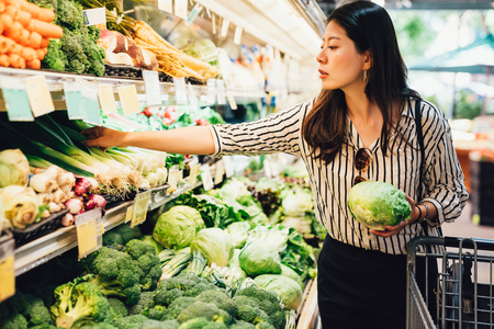 Foto de asian local woman buy vegetables and fruits in supermarket. young chinese lady holding green leaf vegetable and picking choosing green onion on cold open refrigerator. elegant female grocery shopping - Imagen libre de derechos
