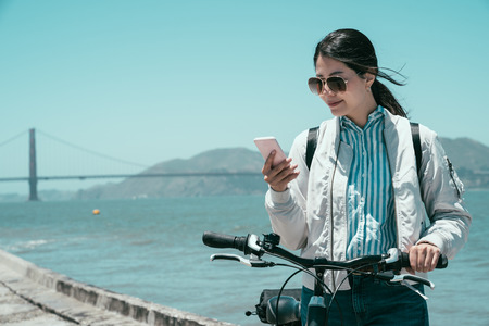 Photo pour girl traveler walk with bike in summer travel in san francisco usa. golden gate bridge in background with mountain under blue sky. asian woman smiling using mobile phone searching online information. - image libre de droit