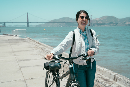 Foto de asian tourist woman in sunglasses using bicycle as means of transportation self guided tour trip in san francisco america in summer. young girl walk with bike near the ocean bay with golden bridge. - Imagen libre de derechos