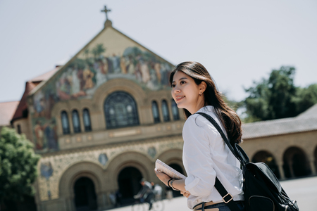 Foto de asian college girl carrying backpack and school book walking to church praying in the morning before go to class in university. - Imagen libre de derechos