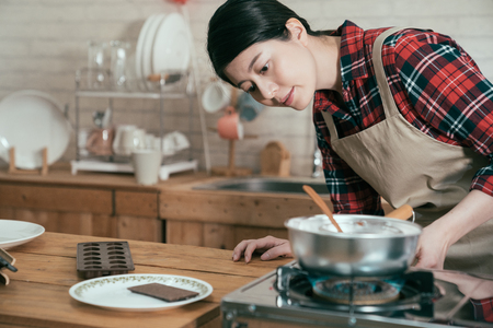 Foto de young chinese girl in pinafore turning on burner to cook meal. woman in apron open stove on fire to melt chocolate handmade dessert for valentine day gift for husband. elegant female prepared present - Imagen libre de derechos