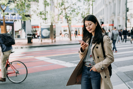 Foto de elegant asian office lady standing in city street using cellphone replying texting message. many people walking on zebra cross to protect pedestrian safety. young woman smiling with bike riding pass - Imagen libre de derechos