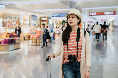Photo pour young girl pass the e gate walk in lobby airport shopping tax free area. lady passenger going to departure gate with luggage. beautiful woman in hat camera relax indoor through specialty local shop - image libre de droit