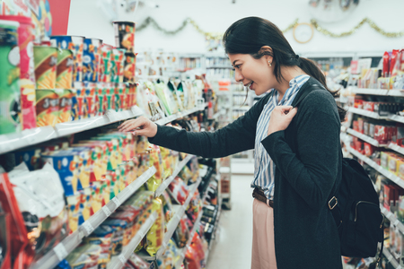 sale shopping consumerism people concept. asian woman backpacker with curious face picking snack cookies choose at grocery supermarket. lady buying products food instant noodles in convenience store.