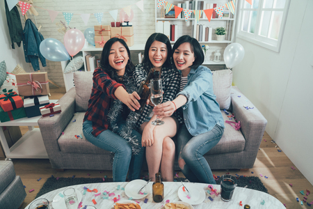 Foto de group of happy women cheers toasting glasses wine with colorful confetti all around the decorated room. cheerful ladies clinking champagne celebrating party. presents gift boxes balloons in house. - Imagen libre de derechos