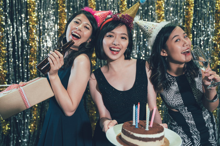 three young ladies cheerfully smiling holding cake and gift boxes face camera. group of best friends celebrating birthday at nightclub wearing funny party hats drinking alcohol. sexy women having funの写真素材