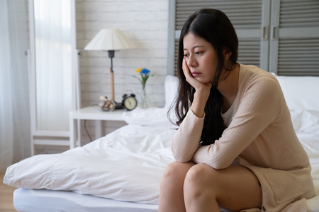 Photo pour Sad depressed  woman with smock jacket suffering from insomnia sitting in bed. thoughtful girl touching her face sleep disorder and stress concept. asian female resting at home in day time - image libre de droit