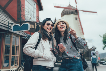 two asian women travel in copenhagen denmark lifestyle in spring season. girls backpackers with hat standing on street city with windmill in background outdoor. female tourist point holding cellphoneの写真素材