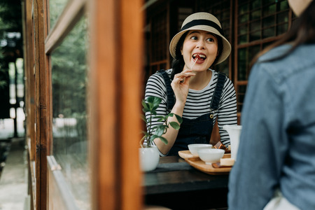 two happy girls spend time together travel osaka japan. Beautiful asian women relaxing enjoy japanese local sweets in traditional wooden house by summer garden. friends drinking matcha tea and snacks