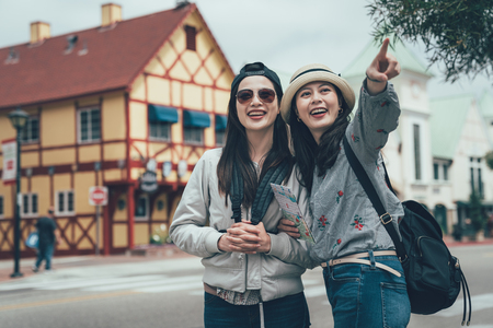 two happy girl friends holding map and pointing finger outdoor in copenhagen denmark.の写真素材