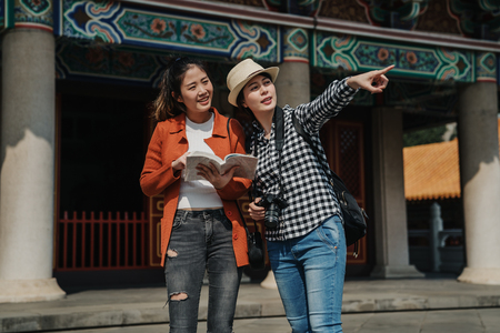 young travelers holding guide book discussing about information and another female tourists point finger showing.