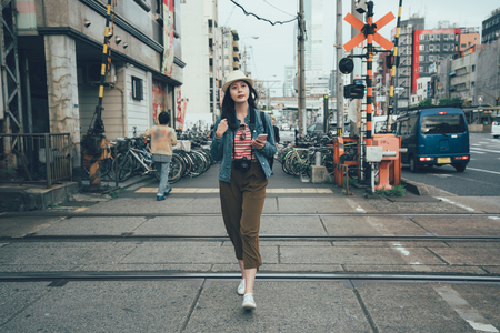 full length young beautiful asian woman crossing the train tracks while sightseeing traveling in osaka japan. girl walking on road railway outdoor in busy city with car driving in background
