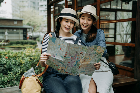 two asian girls in casual outfit wear straw hats looking at map and searching destination sitting outside japanese wooden house in zen teien garden travel in tokyo japan. women travelers check route
